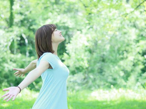 自然の中で胸を張る女性