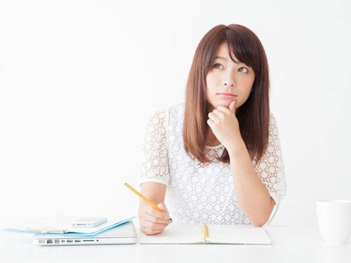 ノートを広げて頬杖をついている女性